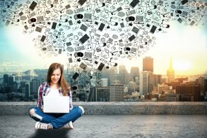 Happy casual woman on rooftop using laptop with abstract media icons above on city background. Social networks concept