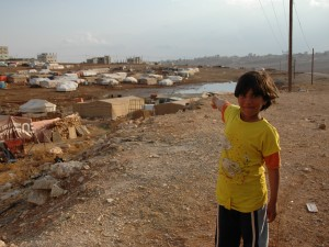 A Syrian refugee girl points at the tented settlement where she lives with her family in Jawa, in the outskirts of Amman, where a mere one hour of rainfall flooded large sections of the camp. Oxfam will be helping refugees living in tented settlement through the distribution of blankets and plastic sheeting to help protect the tents better from the rain and snow.